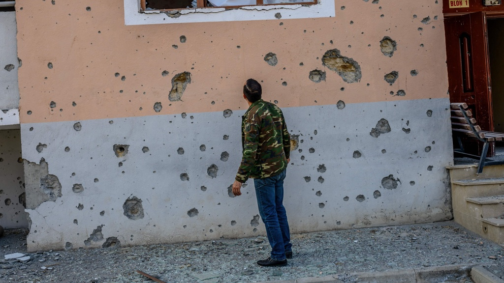 Movsumov Qowkar, 32, checks his neighbor's home damaged by shelling in the city of Terter early on Sunday.