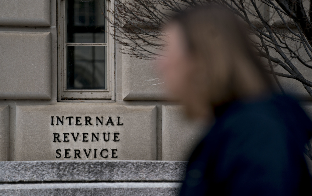 A woman walks past an IRS building.