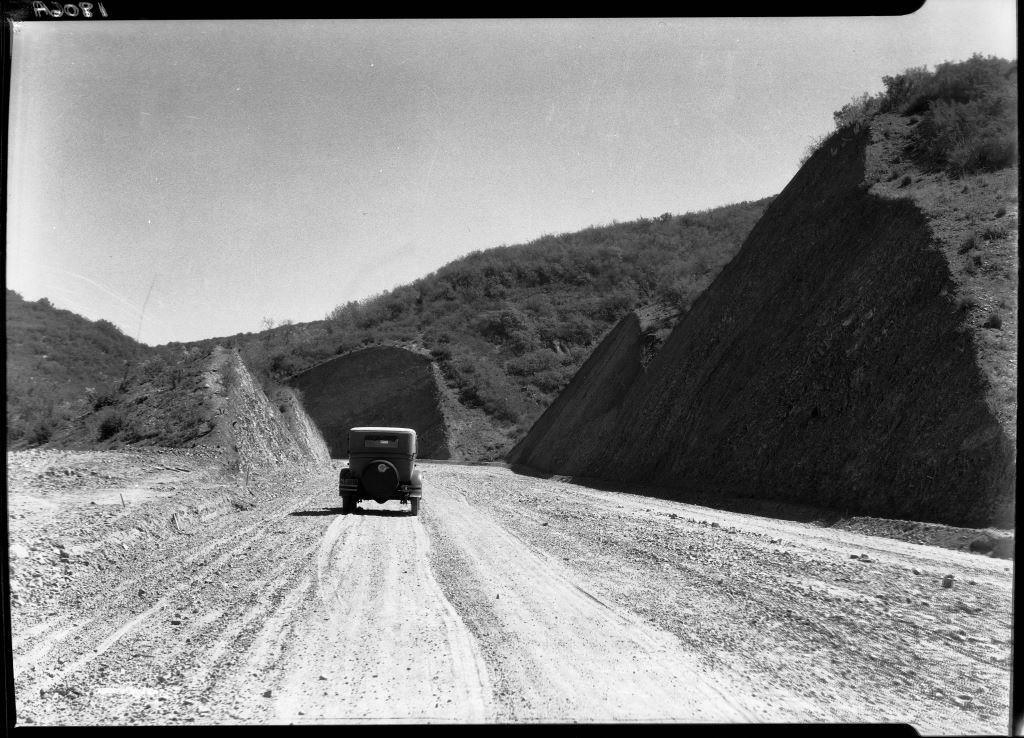 The unpaved Sepulveda Boulevard after completion in 1930. The hills have been cut back to widen the roadway, which is paved with graded gravel, as it was for most of the hilly portion of the road.  Hard pavement was added incrementally over the new 20 years.