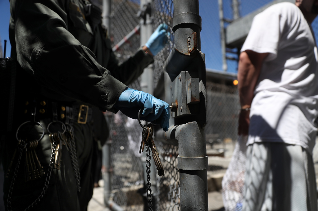 A California Department of Corrections and Rehabilitation (CDCR) officer opens the gate for an inmate leaving the exercise yard at San Quentin State Prison on August 15, 2016 in San Quentin, California.