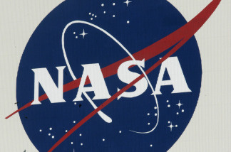 Birds fly past a NASA logo on the Vehicle Assembly Building  at Kennedy Space Center.