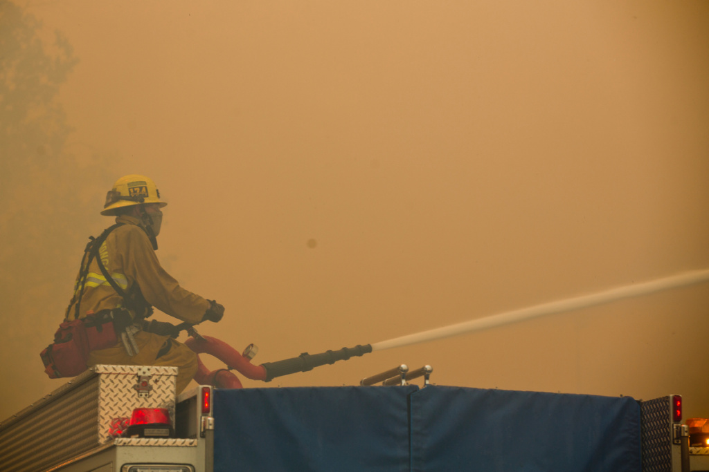 Firefighters fight flames from across Banyan Street using a hose on top of a fire truck as the Etiwanda Fire burns in Rancho Cucamonga on Wednesday, April 30, 2014.