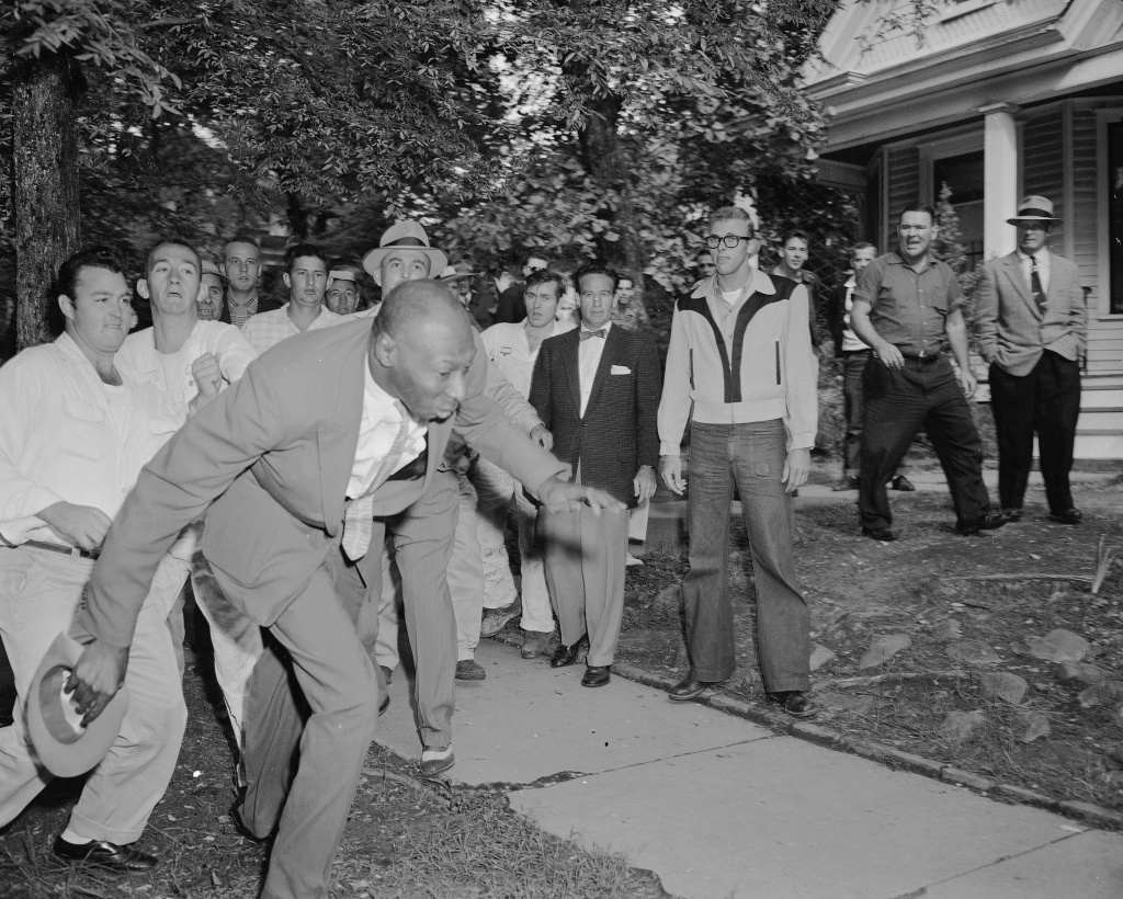 In this Sept. 23, 1957 file photo, a reporter from the Tri-State Defender, Alex Wilson, is shoved by an angry mob of white people near Central High School in Little Rock, Ark. The fight started when nine black students gained entrance to the school as the Army enforced integration.