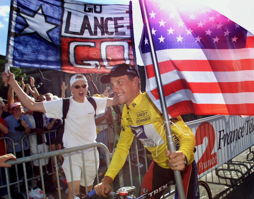 The winner of the 1999 Tour de France American Lance Armstrong is supported by spectators during his honour lap on the Champs Elysees in Paris, 25 July 1999.
