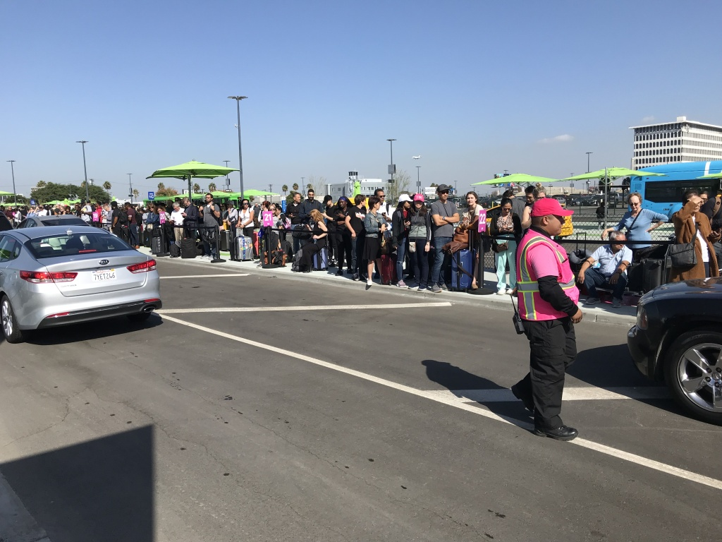 Passengers cluster together, waiting for Lyft rides at LAX's new rideshare pickup zone, Oct. 29, 2019.