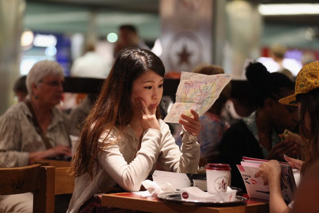 A woman studies a map of the London Underground network in a cafe.