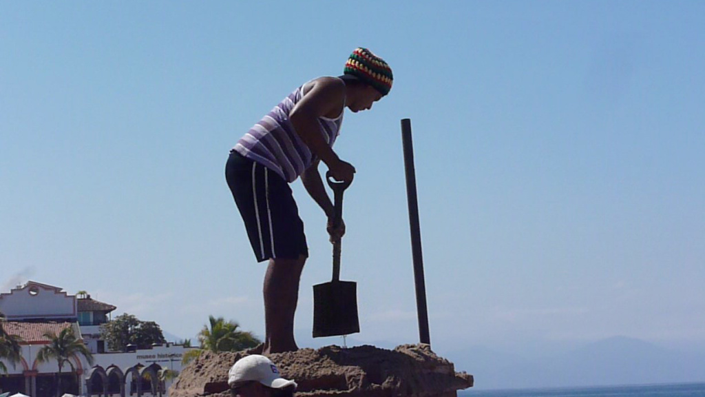 A man bends with a beautiful hip hinge in Puerto Vallarta, Mexico.