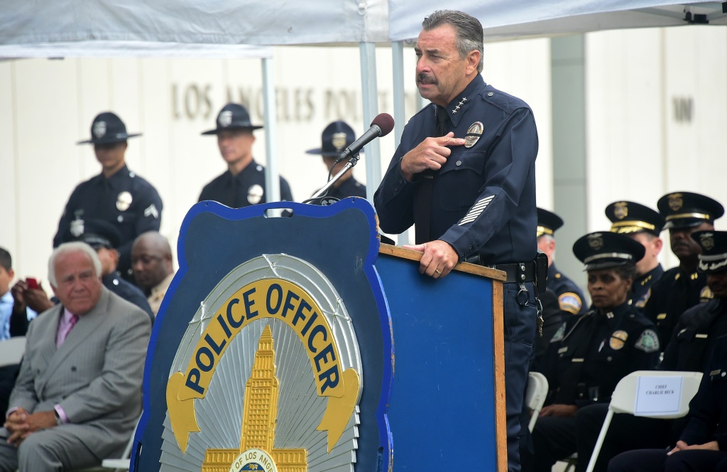 Los Angeles Police Chief Charlie Beck points to the black ribbon on his badge while addressing police recruits at their graduation ceremony on July 8, 2016 in Los Angeles, California.