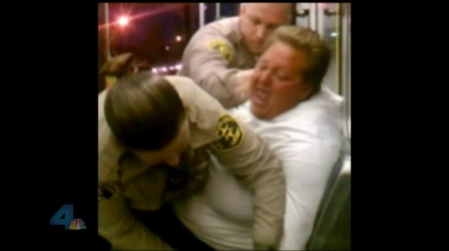 Screenshot via NBC of cellphone footage from the night Army veteran Julie Nelson was being detained by two law enforcement officials. Nelson admits cursing during the altercation, but denies acting out with physical violence.
