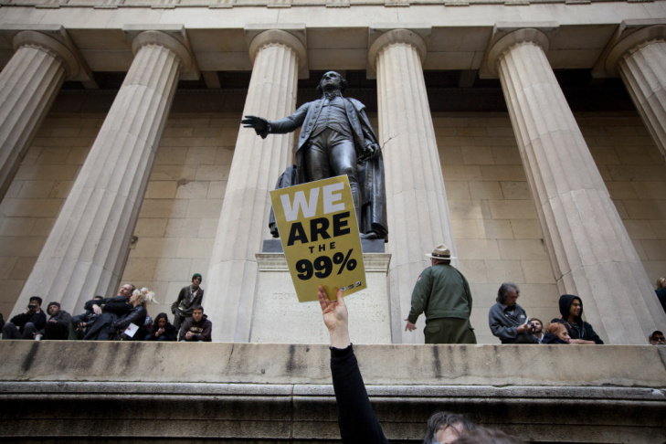 A demonstrator with the Occupy Wall Street holds up a 99% sign in front of the George Washington statue at Federal Hall during a rally on Wall Street on March 30, 2012 in New York City.