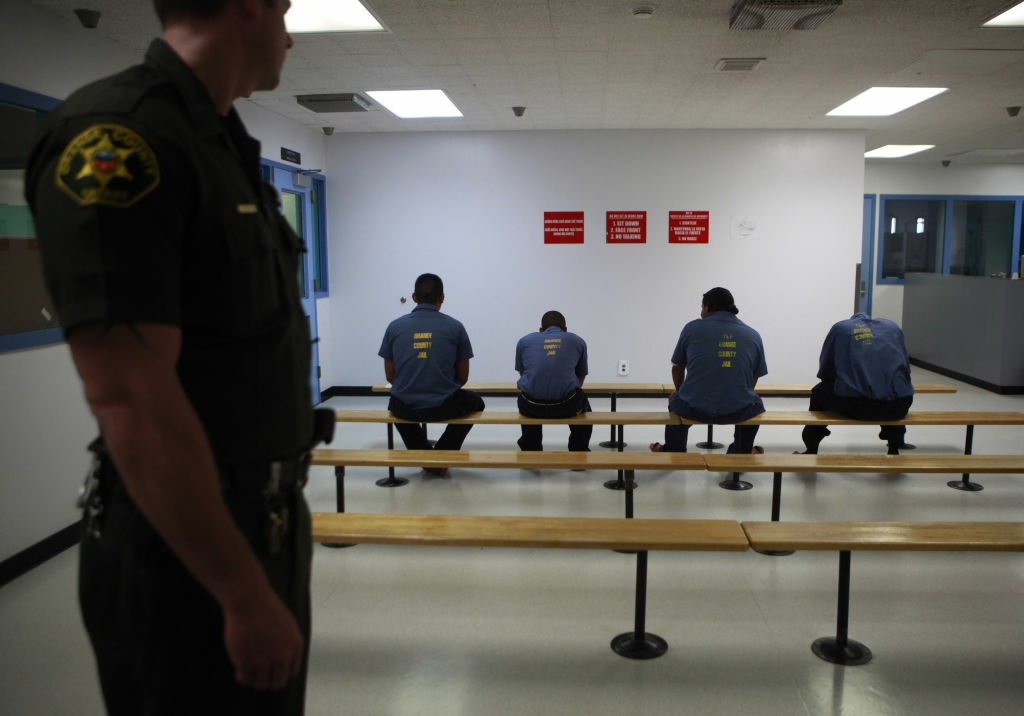 An Orange County Sheriff's deputy keeps watch over a group of immigrant detainees at the Theo Lacy Facility, where the federal government contracts detention space. Immigrant detention is among the issues being weighed by a Senate committee as it debates amendments to an immigration reform bill.