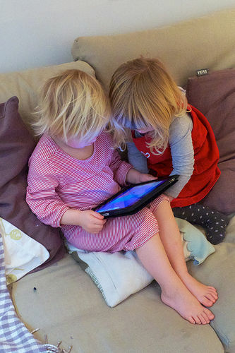 Two children focused on an iPad. Is it good for them?
