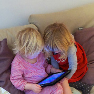 Two children focused on an iPad