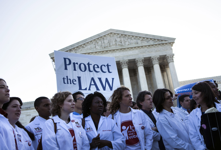 Demonstrators for and against the Patient Protection and Affordable Care Act march and chant in outside the U.S. Supreme Court Building on March 26, 2012 in Washington, D.C.