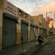 A homeless man walks down the street as a new day begins in Skid Row, where the homeless have waken up before dawn to dismantle their beds and encampments before businesses open.