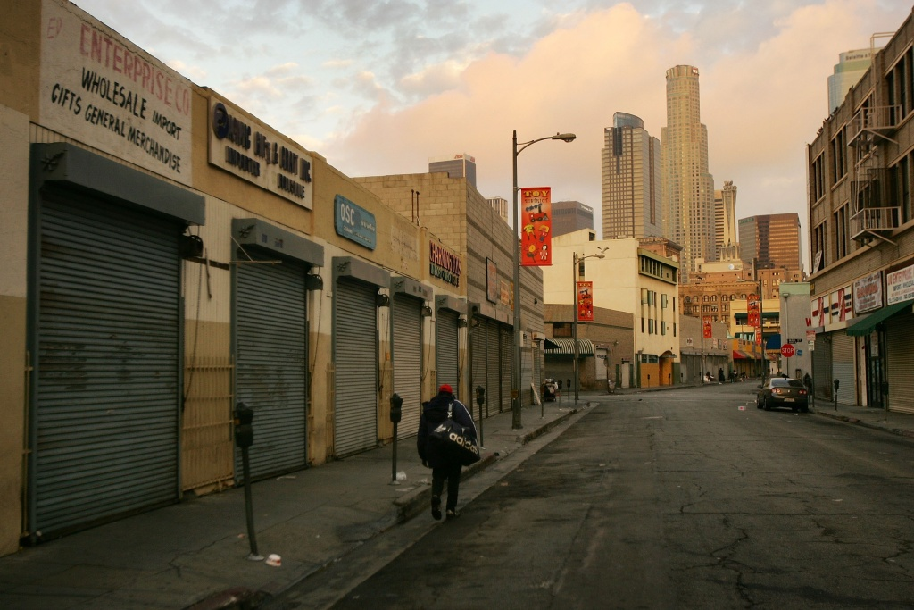 A homeless man walks down the street as a new day begins in the Wall Street area in the downtown Skid Row area of Los Angeles, California.