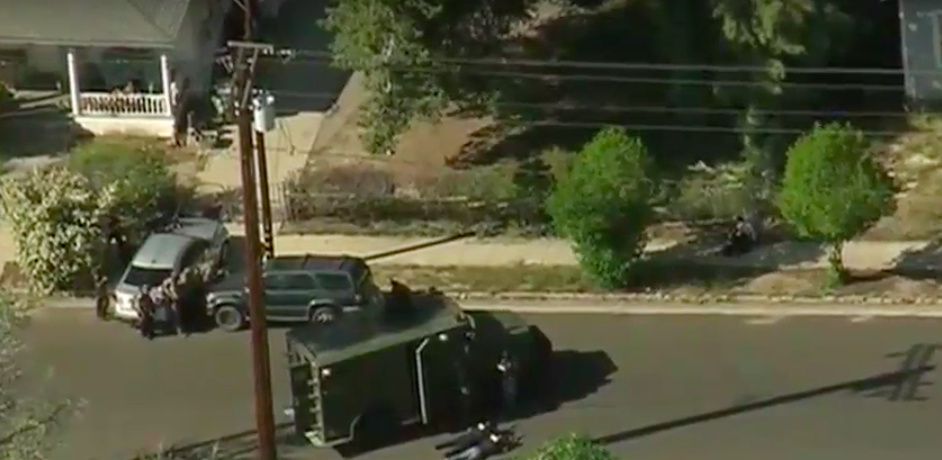 A television news shot of the two-hour standoff in Redlands in which police killed an armed man who was holding his ex-girlfriend hostage. In this image the man is holding the woman on the sidewalk between the two bushes. Police said they opened fire when the man fired his gun at the woman. She was taken to a hospital where she was listed in critical condition.