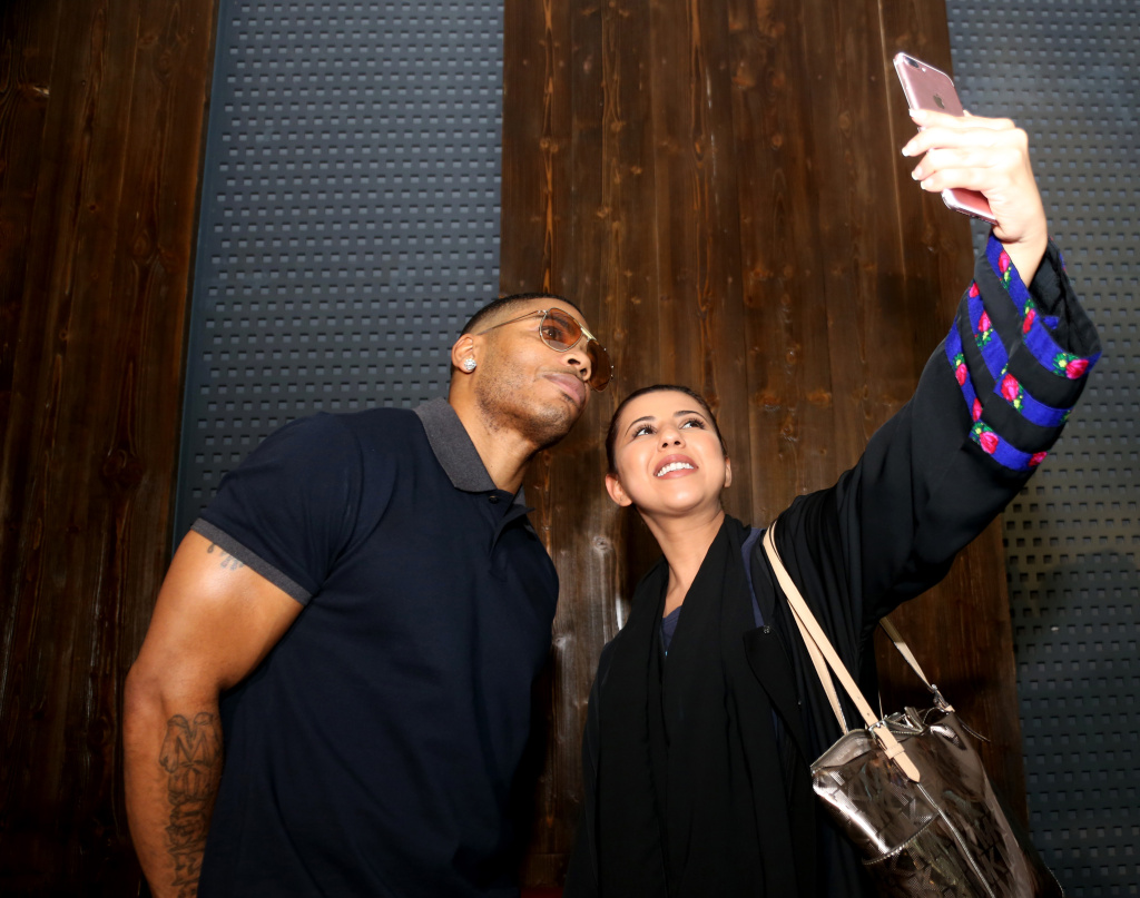 US rapper Nelly (left) poses for a picture with a fan ahead of a male-only concert at King Abdullah Economic City on December 14, 2017.