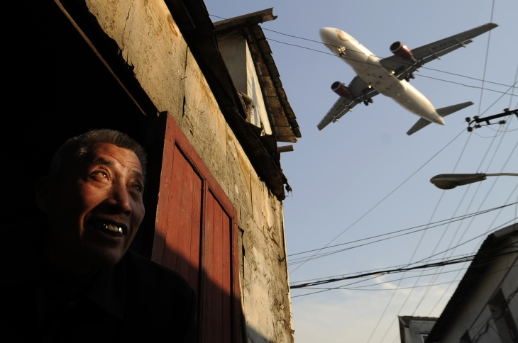 A man watches as an airliner flies over