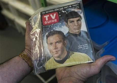 In this Friday, Nov. 30, 2012 photo, James Comisar holds an original TV Guide issue featuring William Shatner, and Leonard Nimoy of