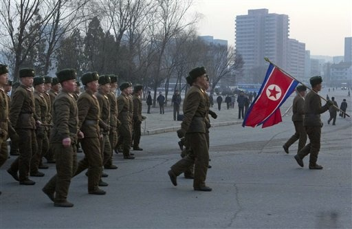 North Korean soldiers, led by their national flag bearers, march on a street in Pyongyang, North Korea on Saturday, March 16, 2013.