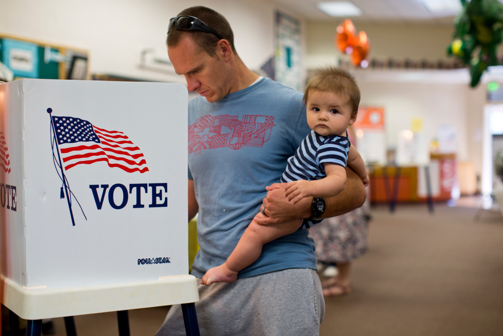 Jeff Thompson holds his 8-month-old son, Tyler, while voting in the Los Angeles County primary election at Canyon Springs School's library on Tuesday, June 3, 2016, in Santa Clarita.