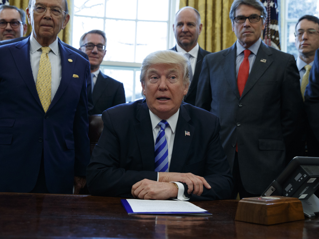 President Trump, flanked by Commerce Secretary Wilbur Ross (left), and Energy Secretary Rick Perry (right), in March 2017, announcing the approval of a permit to build the Keystone XL pipeline. On Monday two Native American tribes filed a lawsuit seeking a judge to rescind the permit for the $8 billion project.
