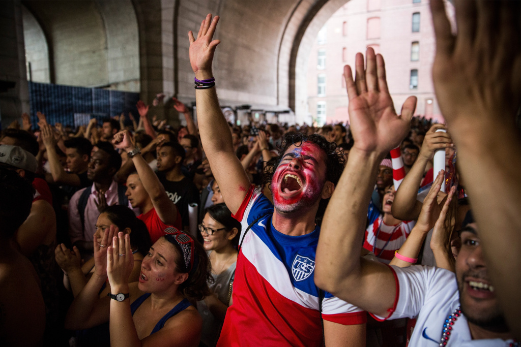 Christian Raja, of Brooklyn, reacts while watching the United States versus Belgium game in the World Cup on a projected screen under the Manhattan Bridge on July 1, 2014 in the Dumbo neighborhood of the Brooklyn borough of New York, United States. This week, the US plays host for the first time for the Copa América tournament, bringing the best teams from the region to US cities.