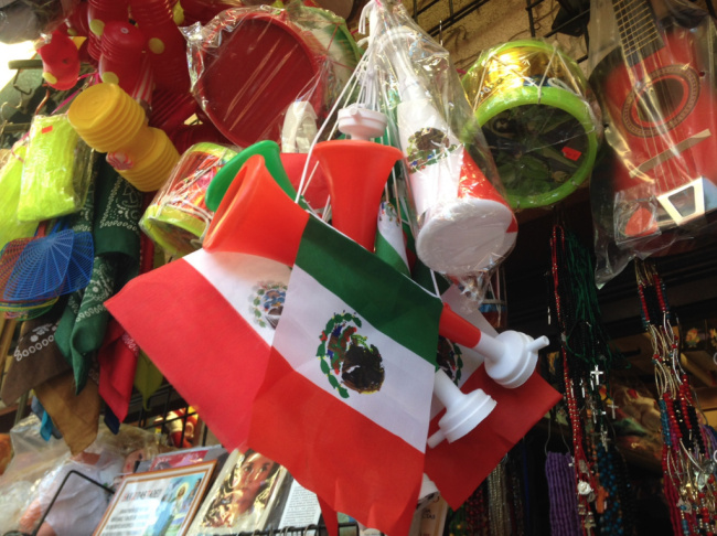 Ana Rosa Ornelas holds up the Mexican flag that Cesar Gil, left, plans to take to the Rose Bowl for the big U.S.-Mexico soccer match.