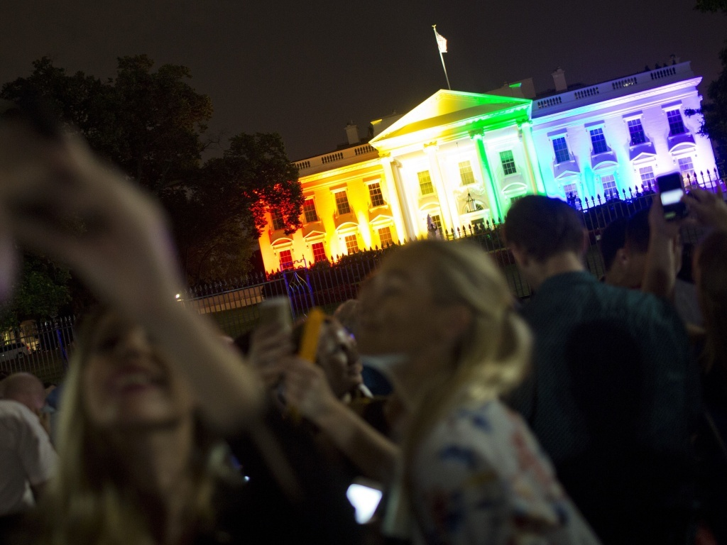 Crowds of people take photos of the White House lighted in the rainbow colors in Washington on June 26, 2015.