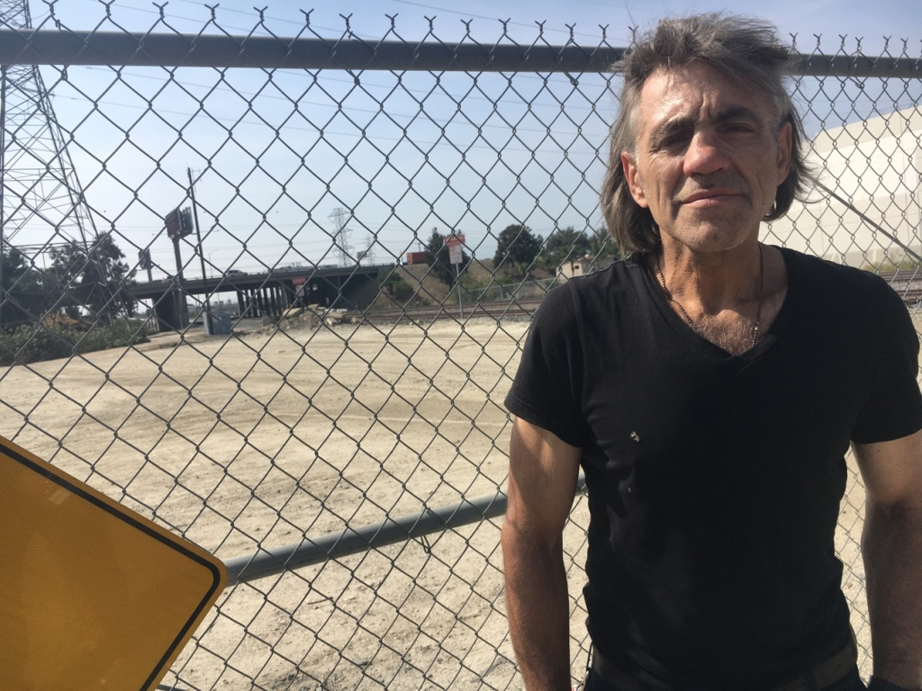James Russell Stannard, 57, an Air Force veteran, stands by a fence that blocks traffic into a dry ravine in El Monte. He said he's been homeless in the area for about 3 years. Veterans say about 100 homeless people live in the area, where the busy 605 Freeway meets the 10 Freeway.
