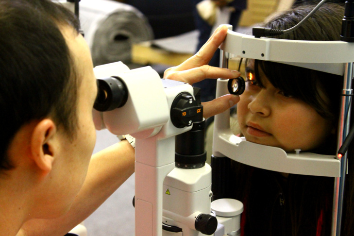 A trained optician checks the retina and blood supply to a young student's eyes.