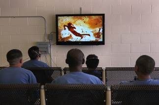 Detainees watch a movie in an indoor recreation area at a U.S. Immigration and Customs Enforcement detention facility on July 30, 2010 in Florence, Arizona.