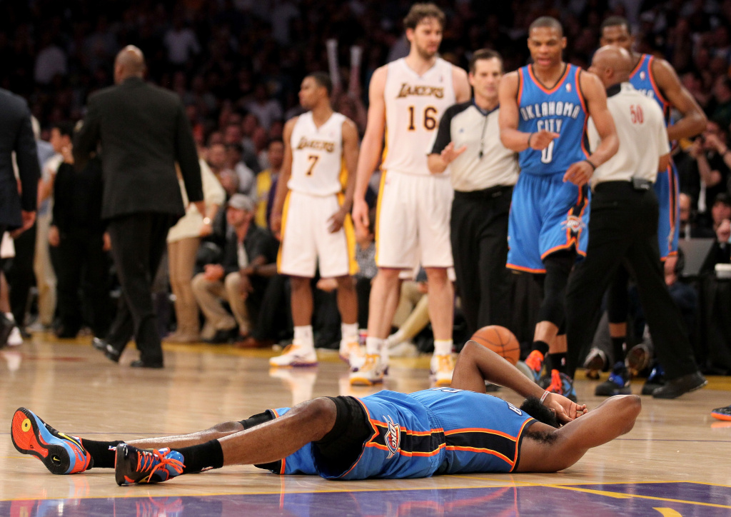 James Harden #13 of the Oklahoma City Thunder lies on the floor after being hit by Metta World Peace #15 of the Los Angeles Lakers as referees separate Thunder and Lakers players at Staples Center on April 22, 2012 in Los Angeles, California.
