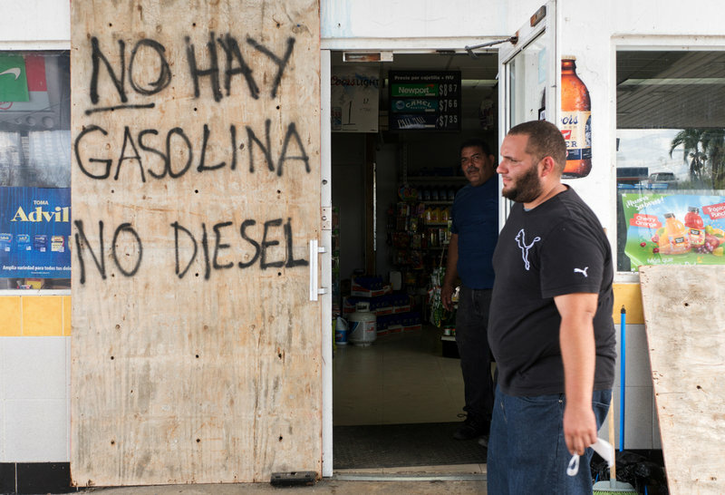 Manager Carlos de Armas walks by the entrance to the Gulf Route 65 gas station as people wait for a tanker truck to arrive.