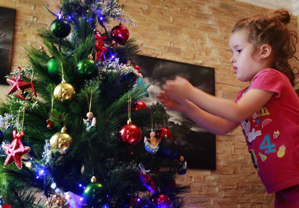 Four-year old Vera Martin prepares the Christmas tree at her home on the island of Tenerife on December 8, 2013.
