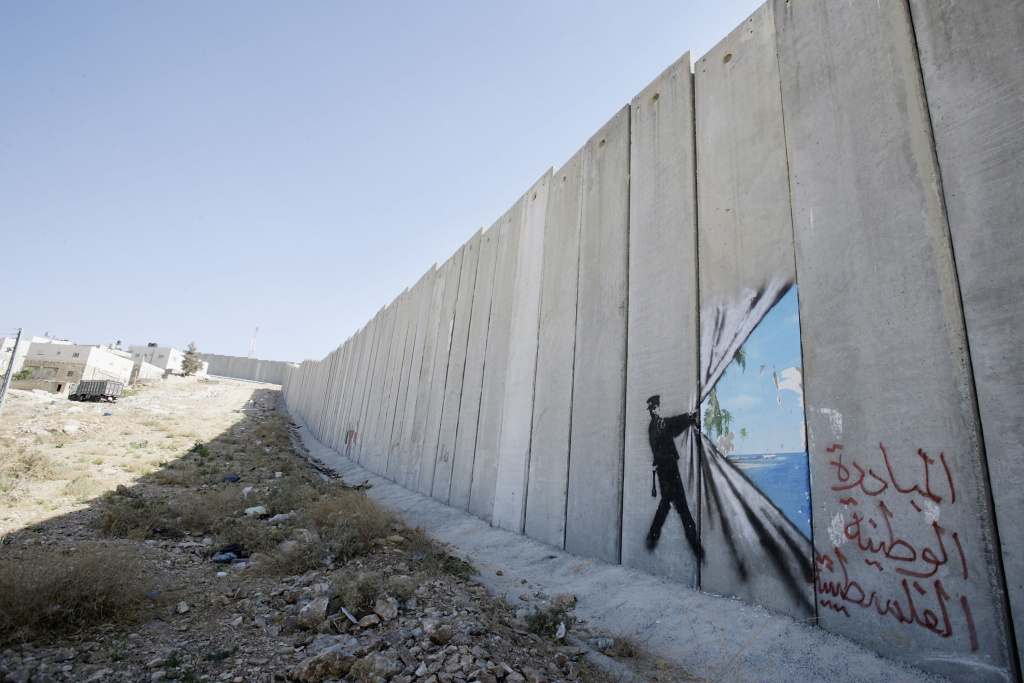 A graffiti made by the graffiti artist Banksy is seen on Israel's highly controversial West Bank barrier in Abu Dis on August 6, 2005.