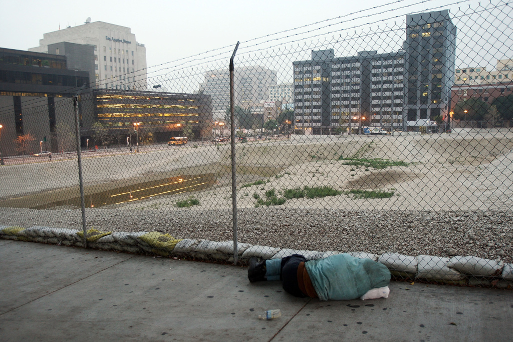 A homeless man sleeps on the sidewalk next to a prepared downtown lot where the new Los Angeles United States Courthouse is supposed to be built but is idle on March 20, 2009 in Los Angeles, California.