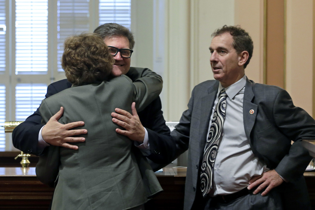 FILE - In this April 30, 2015 file photo, state Sen. Bob Hertzberg, D-Van Nuys, center, gives Sen. Lois Wolk, D-Davis, a hug as Sen. Bob Wieckowski, D-Fremont, looks on at the Capitol in Sacramento. Hertzberg has been told to stop hugging people after a sexual misconduct investigation concluded his behavior made multiple colleagues uncomfortable. Hertzberg was formally reprimanded Tuesday, March 6, 2018, by the Senate Rules Committee. The Los Angeles-area says he will respect the request not to hug people.