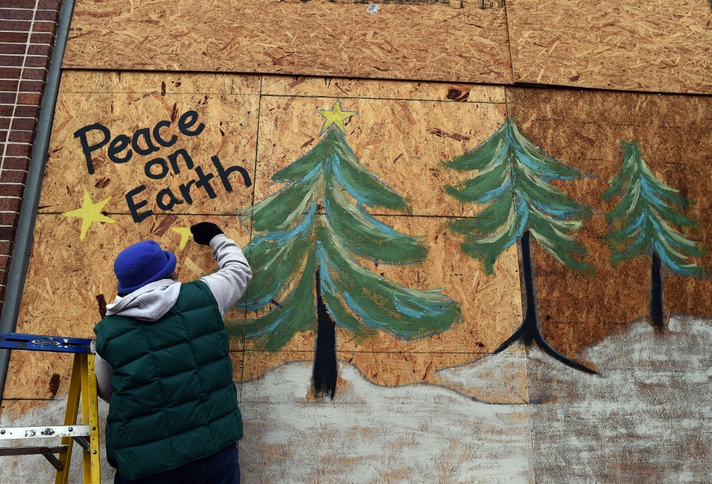 Karen Gold paints on a boarded window of her store in Ferguson, Missouri, on November 26, 2014.