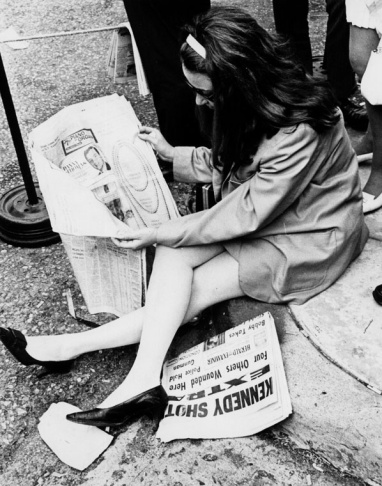 Woman reading newspaper, an