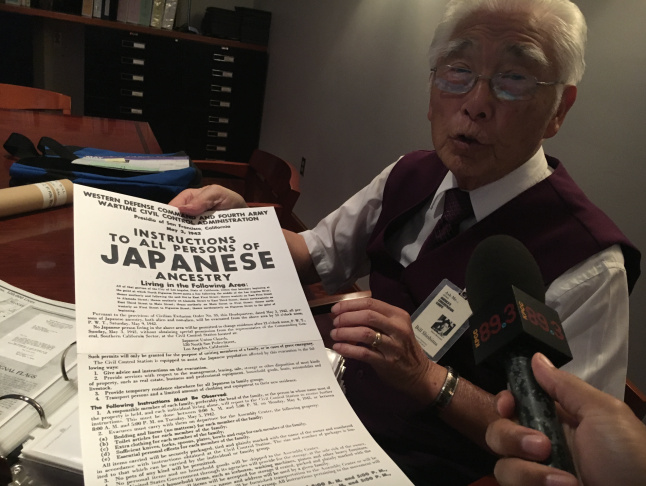 Bill Shishima holds up a replica of the poster that appeared in his neighborhood.