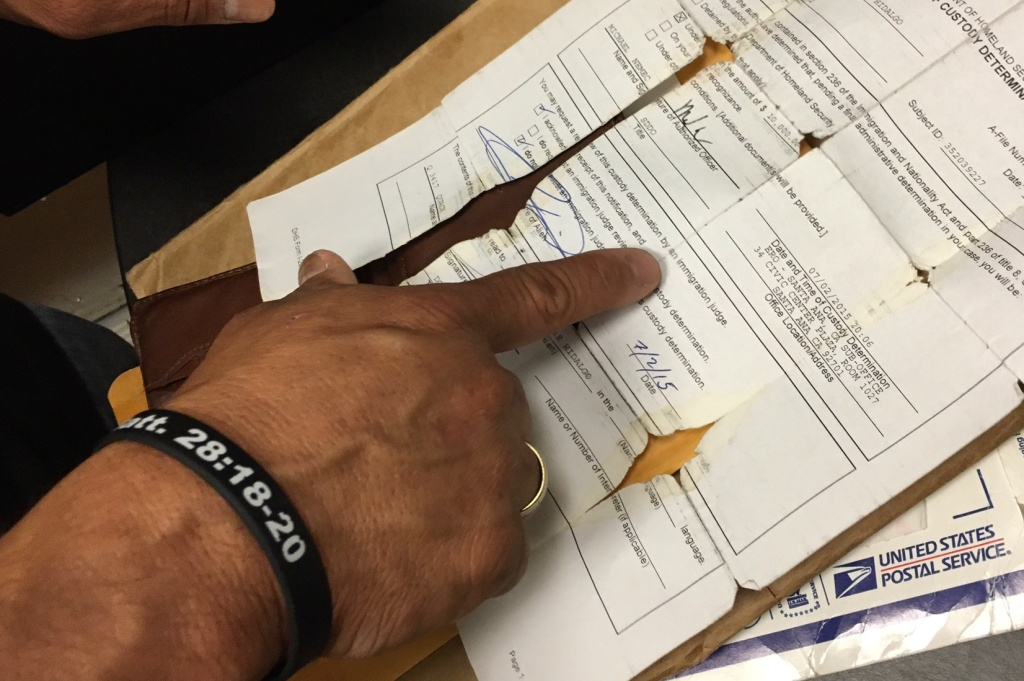 Carlos Hidalgo points to an original document from his time in ICE detention that ended in 2015. He said he keeps the paperwork in his wallet as a reminder of his time at the privately-run facility in Adelanto, California.