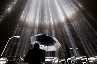 A worker holds an umbrella while adjusting beams of the Tribute in Lights ahead of the tenth anniversary of the September 11 terrorist attacks on September 7, 2011 in New York City.