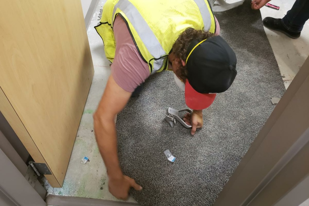 Workers at Joint Base San Antonio-Lackland rip up carpet in a dorm as part of a basewide effort to clean up mold.