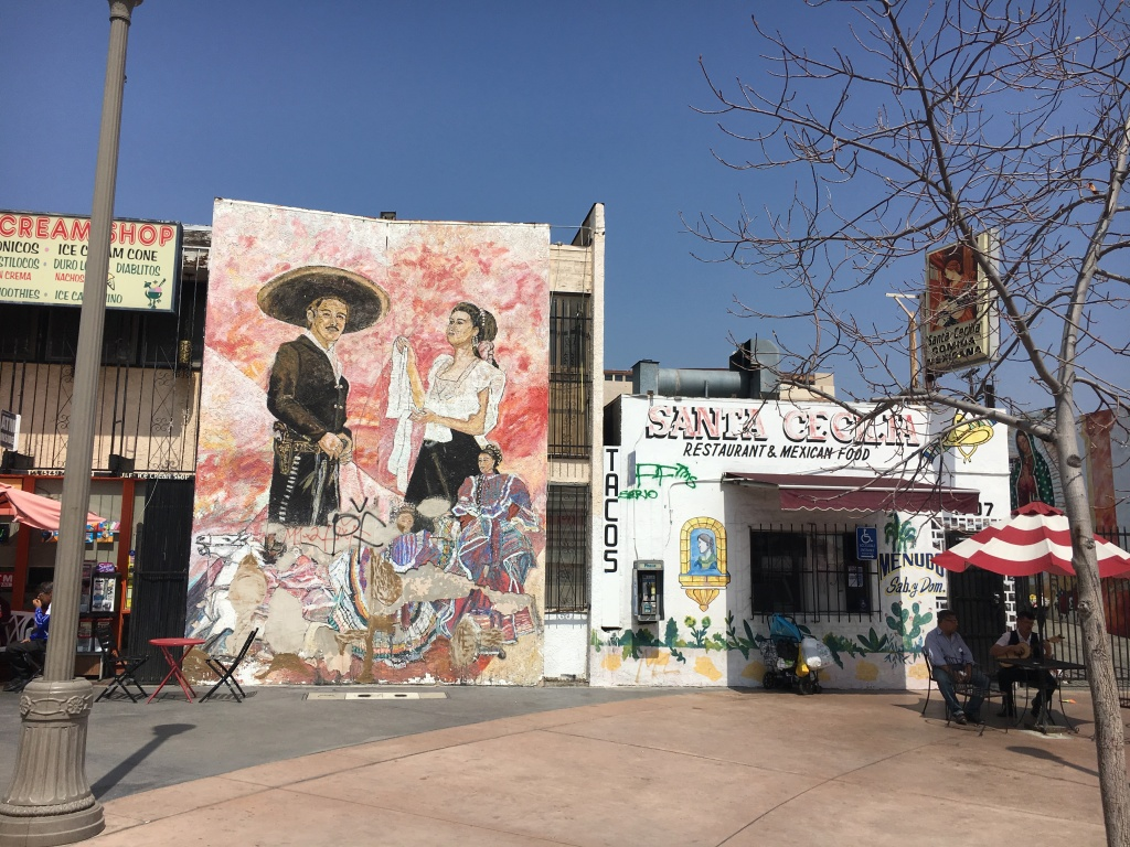 During the LA Cycle taco tour, there's a stop at Mariachi Plaza. Here you can see two Mariachis beneath the shade of an umbrella.