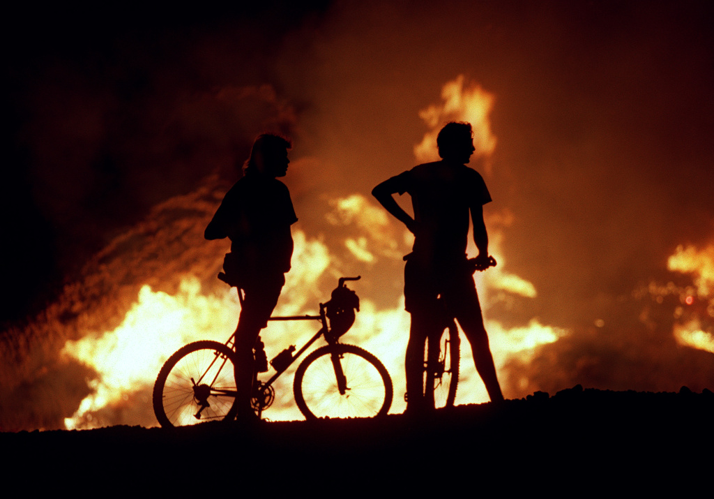 File: Residents use bicycles to get close enough for a good look a raging fire in nearby Laguna Beach On Oct. 28, 1993, shortly before their neighborhood was evacuated.