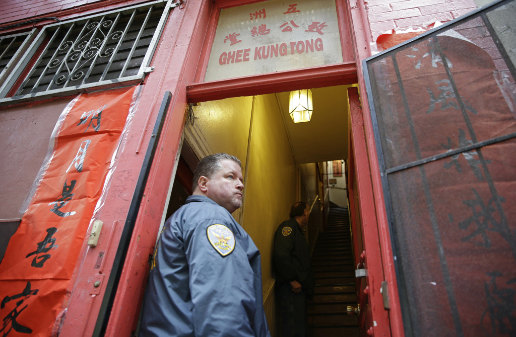 A San Francisco police officer stands watch as police and FBI agents search a Chinatown fraternal organization, Wednesday, March 26, 2014, in San Francisco. California State Sen. Leland Yee was arrested Wednesday during a series of raids by the FBI in Sacramento and the San Francisco Bay Area, authorities said.