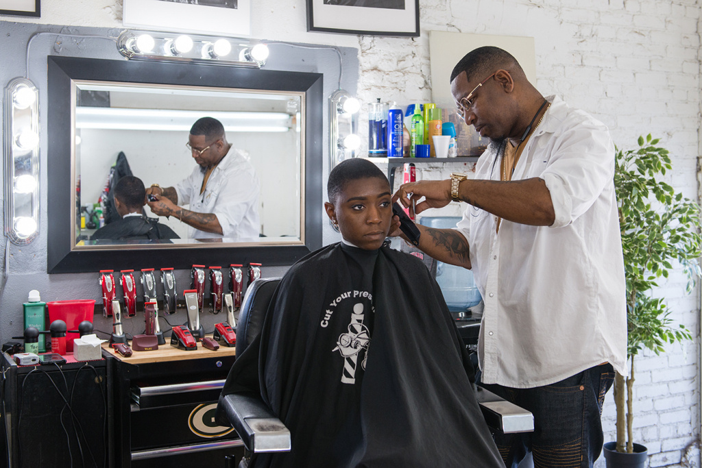 Corey Thomas works on a client at A New You barbershop in Inglewood.
