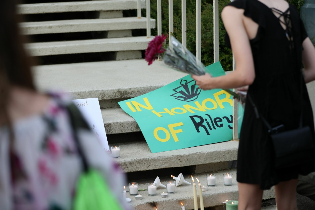 Students lay candles and flowers at the steps of Kennedy Hall to honor the victims of a shooting the day earlier at the University of North Carolina Charlotte,including Riley Howell.